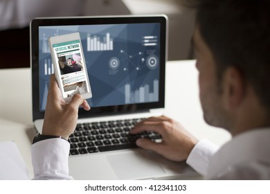 businessman distracting at work with smartphone showing social network on screen. All screen graphics are made up.