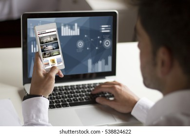 businessman distracting at work with smartphone showing magazine on screen. All screen graphics are made up.