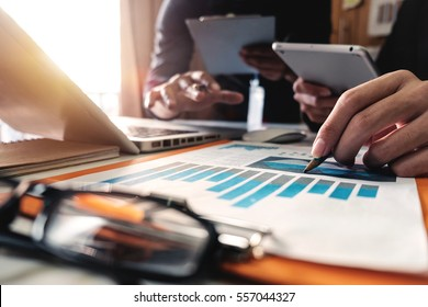 businessman documents on office table with smart phone and laptop and two colleagues discussing data in the background in morning light