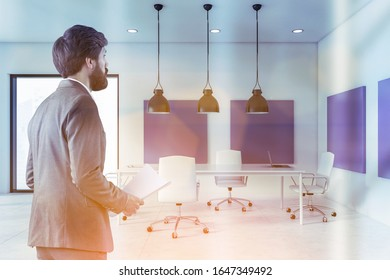 Businessman with documents standing in stylish meeting room with white and purple walls, tiled floor and long conference table with white chairs. Toned image