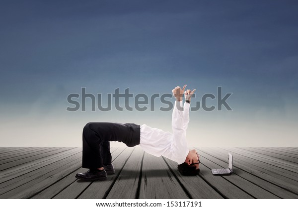 Businessman doing bridge yoga over blue sky background