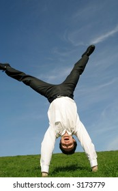 Businessman doing cartwheel outdoors