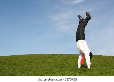 Businessman doing handstand outdoors