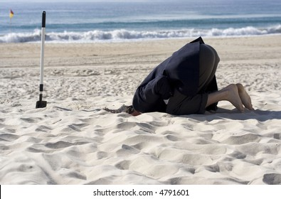 Businessman doing his up most to avoid the business day by burying his head in the sand