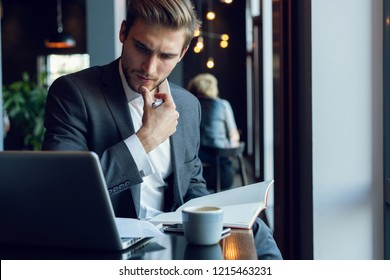 Businessman doing his work and having coffee in cafe.