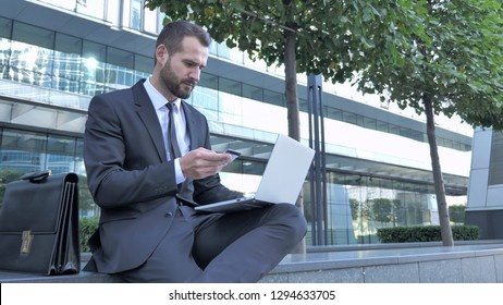 Businessman Doing Online Payment via Laptop Outside Office