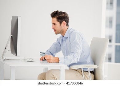 Businessman doing online shopping on computer in office