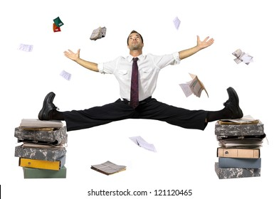 Businessman doing splits over stack of files with papers all around