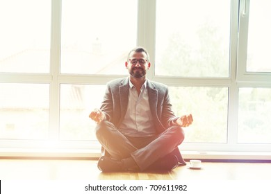 businessman doing yoga in lotus pose