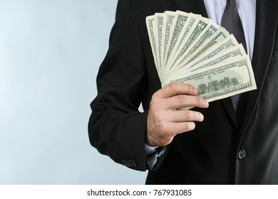 Businessman with dollar bills on light background, closeup