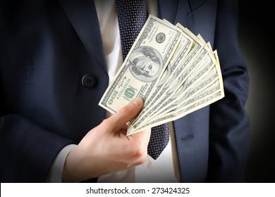 Businessman with dollars in hands on dark background