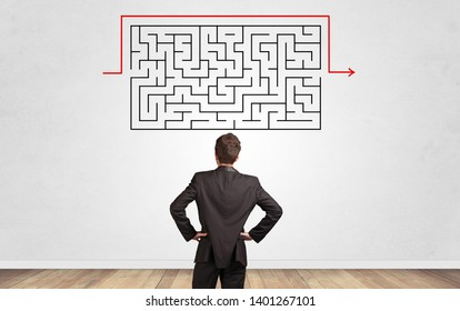Businessman in doubt looking to a maze and searching the way out