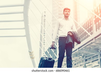 Businessman drag luggage and hold suit in city outdoor on building background. Concept of business trip and work life balance. Image processing instagram color.