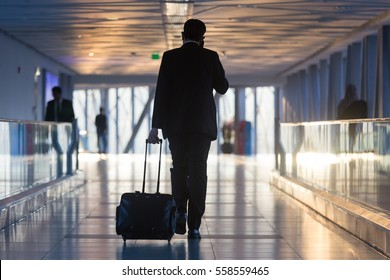 Businessman dragging a small carry on luggage suitcase at airport corridor walking to departure gates.
