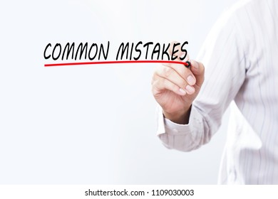Businessman draw COMMON MISTAKES word with red marker on transparent wipe board, business concept. Training Planning Learning Coaching Business Guide Instructor Leader concept.