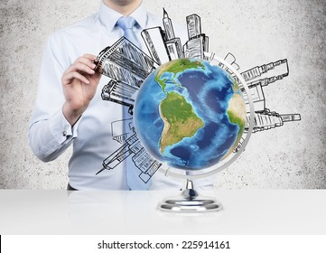Businessman drawing buildings around the world (Latin America views). Elements of this image furnished by NASA
