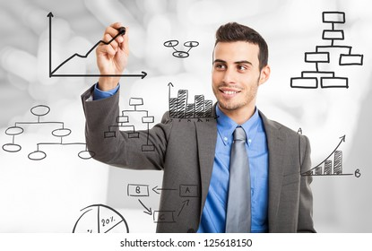 Businessman drawing business concepts on the screen