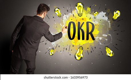 businessman drawing colorful light bulb with OKR abbreviation, new technology idea concept