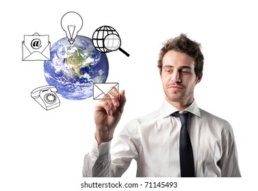 Businessman drawing communication symbols around the earth