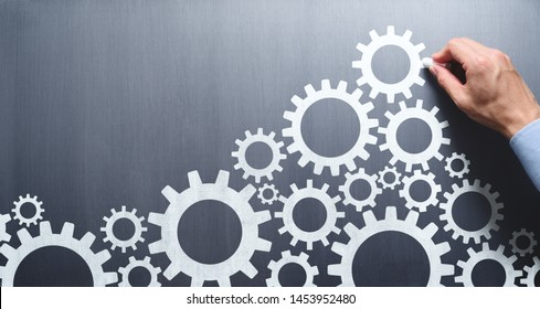 Businessman drawing gears on chalkboard. Development and solutions concept.