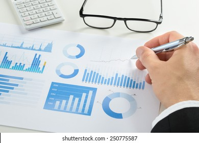Businessman Drawing Graph On Document With Eyeglasses And Calculator On Desk