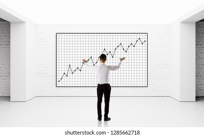 Businessman drawing graphics on wall. Presentation of success marketing plan