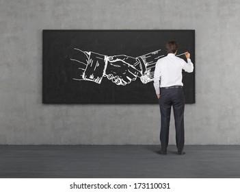 Businessman drawing handshake in a chalkboard