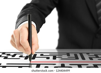businessman drawing labyrinth on a white background