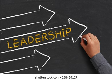A businessman is drawing Leadership concept with arrows on blackboard.