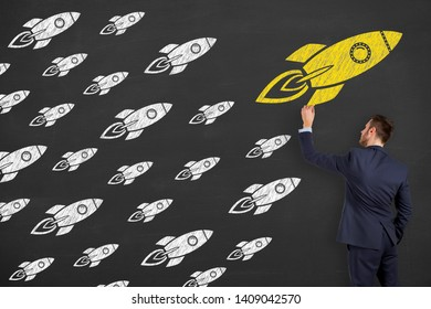 Businessman Drawing Leadership Concepts with Rocket on Chalkboard Background