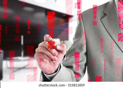 Businessman drawing a red exclamation mark. Business concept.