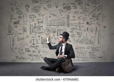 Businessman drawing schemes on a wall