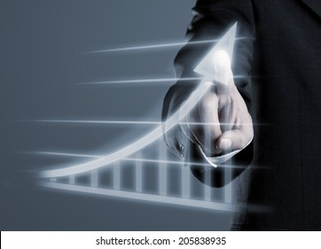 Businessman drawing success graph on virtual futuristic computer display