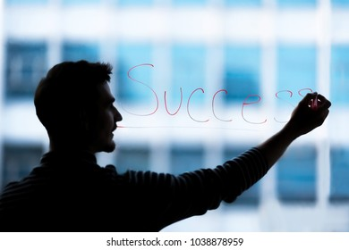 Businessman was drawing SUCCESS word at  glass. Happy business people celebrating success at workplace. Setup studio shooting.