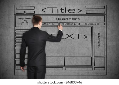 businessman drawing template website on concrete wall