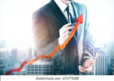 Businessman drawing upward red chart arrow on abstract city background. Growing sales concept. Double exposure