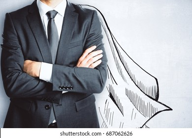 Businessman with drawn cape on concrete wall background. Safety concept