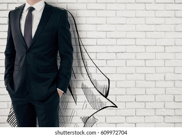 Businessman with drawn cape on white brick background. Leadership concept