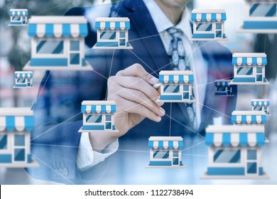 Businessman draws franchise marketing system on blurred background.