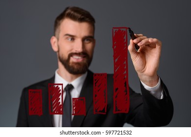 Businessman draws an infographic. A handsome man with a pleasant smile shows activity using a red marker. Business lecture concept.
