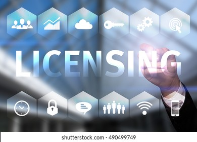 """Businessman draws """"Licensing"""" on the virtual screen. Business concept. Internet concept."""
