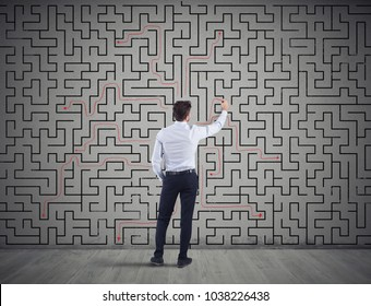 Businessman draws the solution of a labyrinth. Concept of problem solving