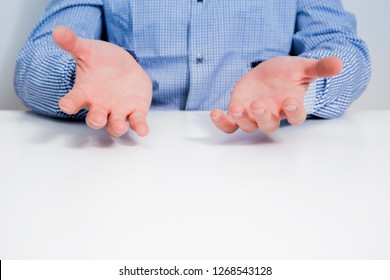 A businessman dressed in a blue checkered shirt sits at the table and spreads his hands in helplessness. The man explains his decisions, the act of helplessness and ignorance.
