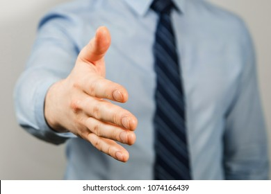 Businessman dressed in blue shirt and tie, extends a hand for a handshake close-up, on gray background