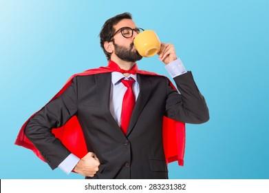 Businessman dressed like superhero drinking coffee