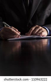 A businessman dressed in a suit sits at a desk and writes in a notebook.
