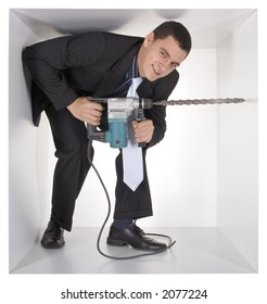 businessman with drill in the cramped white cube
