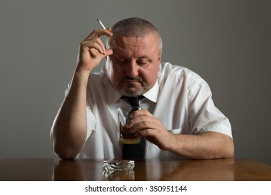 Businessman drinking alcohol and smoking cigarette