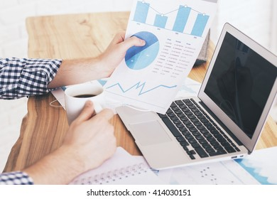 Businessman drinking coffee and analyzing business report at office desk