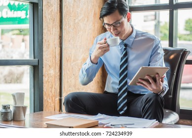 Businessman drinking coffee and holding tablet while reading document before work in the morning.